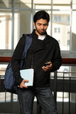 Young Eastern student with cell phone. Inside a College Building Stock Photos