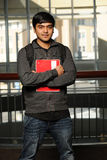 Young Eastern student holding a copybook. Inside a College building Royalty Free Stock Photo