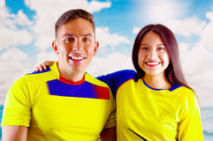 Young ecuadorian couple wearing official Marathon football shirt standing facing camera, very engaged body language royalty free stock images