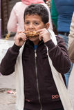 Young Egyptian boy eating roasted ear of corn at Khan Al-Khalili market in Cairo, Egypt. Royalty Free Stock Images