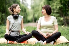 Young and elder woman doing yoga in the park. Young and elder women talking during the morning yoga exercise outdoors in the park Royalty Free Stock Photo