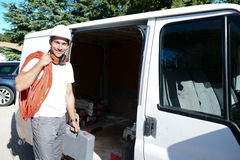 Young electrician artisan taking tools out of professional truck van Stock Images