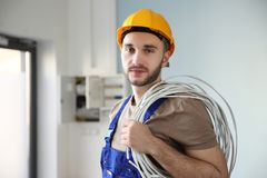 Young electrician with bunch of wires. Indoors Royalty Free Stock Photo