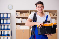 The young electrician with cable working in office Stock Photos