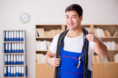 The young electrician with cable working in office Royalty Free Stock Photo