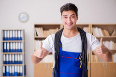 The young electrician with cable working in office Stock Photo