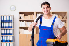 The young electrician with cable working in office Stock Images