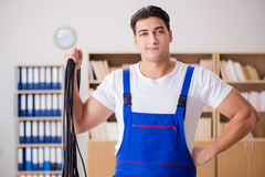 The young electrician with cable working in office. Young electrician with cable working in office Royalty Free Stock Images