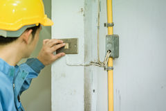Young electrician checking old switch inside building stock photos
