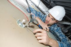 Young electrician fixing neon on ceiling. Young electrician fixing neon on the ceiling Royalty Free Stock Photo