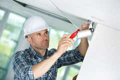 Young electrician in hardhat climbing stepladder Royalty Free Stock Photo