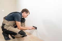 A young electrician installing an electrical socket in a new house. royalty free stock photography