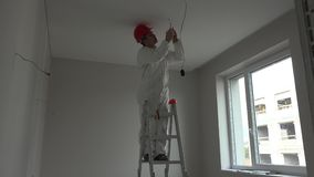Young electrician installing smoke detector fire alarm on ceiling stock footage