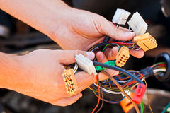 The young electrician man holds the wires Stock Photos