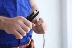 Young electrician skinning a wire. In light room Royalty Free Stock Image