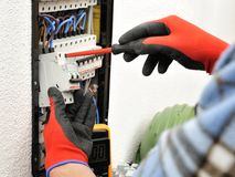 Young electrician technician at work on a electrical panel with. Young electrician technician fixes the electric cable to the magnetothermic switch with the Stock Image