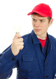 Young electrician in uniform with bulb. Royalty Free Stock Images