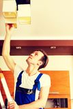 Young electrician working change a bulb at home.  royalty free stock image