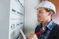 Young electrician working on electric panel royalty free stock photography