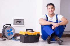 The young electrician working on socket at home. Young electrician working on socket at home Stock Photography