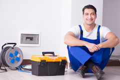 The young electrician working on socket at home Stock Images
