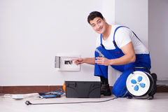 The young electrician working on socket at home. Young electrician working on socket at home Royalty Free Stock Images