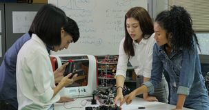 Young electronics engineer team collaborating on construction of robot in the workshop.