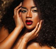 Young elegant african american woman with afro hair. Glamour makeup. Golden Background. stock photos