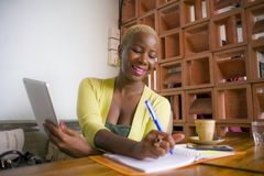 young elegant and beautiful black African American business woman working online with digital tablet pad at coffee shop smiling Stock Photos