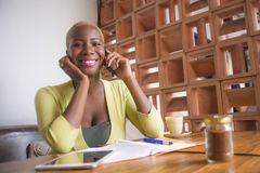 Young elegant and beautiful black African American business woman working online with mobile phone at coffee shop smiling happy stock image