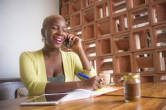 Young elegant and beautiful black African American business woman working online with mobile phone at coffee shop taking notes stock photo