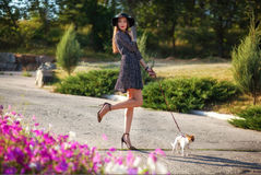 Young elegant beautiful lady with small pretty dog walking in be. Autiful park. Europe style. Wearing hat and silk dress Royalty Free Stock Image