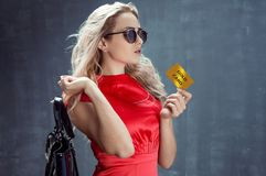 Young elegant blonde with bag on her shoulder. Holds gold card Royalty Free Stock Image