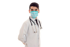 Young elegant brunette doctor in uniform and mask with stethoscope isolated on white background Stock Image