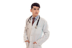 Young elegant brunette doctor in uniform with stethoscope looking away isolated on white background Stock Photos