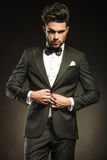 Young elegant business man arranging his tuxedo. Stock Image
