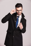 Young elegant business man fixing his glasses Royalty Free Stock Photos