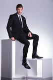 Young elegant business man sitting on a white table Stock Photos