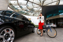 Young elegant business woman with bicycle and car Royalty Free Stock Photo