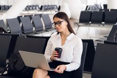 Young elegant business woman in international airport terminal, working on her laptop while waiting for flight royalty free stock photography
