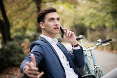 Young businessman talking on smartphone outdoors in a park, looking worried. A young elegant businessman talking on smartphone outdoors in a park, serious Royalty Free Stock Photography