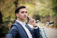 Young businessman talking on smartphone outdoors in a park. A young elegant businessman talking on smartphone outdoors in a park, serious conversation Stock Photography