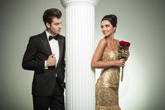 Young elegant couple looking at each other near column. Studio picture Royalty Free Stock Photography