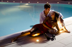 Young elegant couple near the pool. Young couple in love by the pool Stock Images
