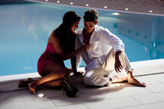 Young elegant couple near the pool. Young couple in love by the pool Royalty Free Stock Images