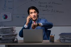 The young elegant financial specialist working in the office night time. Young elegant financial specialist working in the office night time stock photography