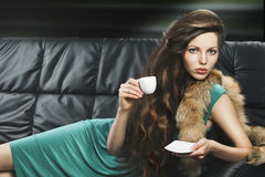 Young elegant girl in green with cup, Royalty Free Stock Photography