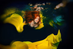 Young elegant girl with red hair posing in the water. Under water in a pool, in yellow Royalty Free Stock Photo