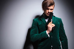 Young elegant hitman  waiting. In green velvet suit with neck bow Stock Images