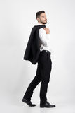 Young elegant luxurious man walking carrying tuxedo over his shoulder looking away royalty free stock photos
